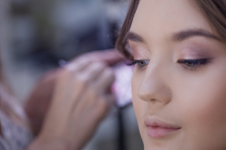 The work of a professional makeup artist. Stylist makeup artist doing makeup and hair in a beauty salon. Professional make-up