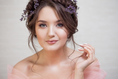 Delicate portrait of a beautiful young woman with hair with braids. Brunette girl with clean fresh skin, spring makeup Stock Photo