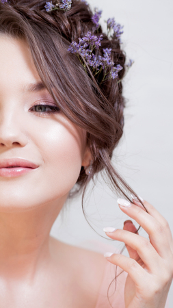 Young brunette woman with beautiful spring look, hairstyle with weave and blue flowers. Skin care, concept