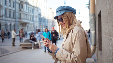 Cute fashionable girl uses apps in phone, shopping and banking. Young woman with phone on the street, lifestyle
