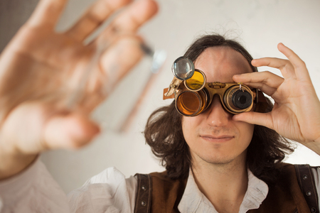 Steampunk style researcher mechanist of the monocle with a large number of lenses looking at something. copy space on the right Imagens