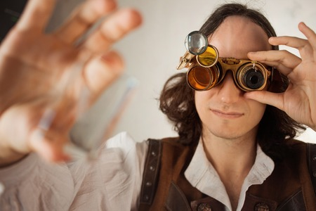 Steampunk style researcher mechanist of the monocle with a large number of lenses looking at something. Young man in leather vest and vintage style