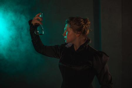 Scientist researcher with a flask of radioactive material. History of science, great physical discoveries. Image in the style of Marie Curie, concept Banco de Imagens