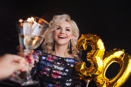 Festive party, young beautiful blonde raises a toast. Birthday party, joy and fun.