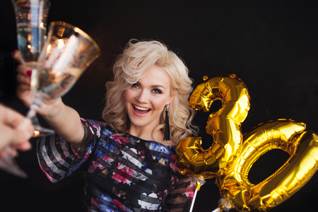 Holiday party, a beautiful young blonde woman drinking champagne. Birthday party, joy and fun.