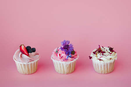 set of delicious cupcakes with different fillings and cream. Three muffins with cream on a pink background, copy space