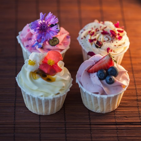 Beautiful and delicious cupcakes on the table. A set of delicious sweet desserts with cream.