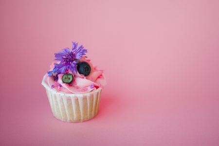 Sweet dessert on pink background, copy space. Cupcake with cream, beautiful and delicious. pink background