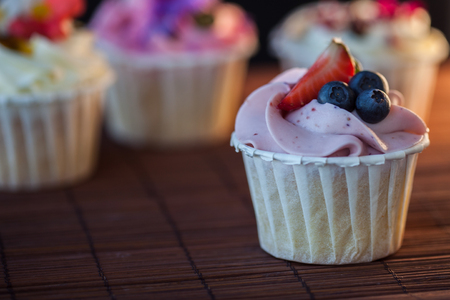 Beautiful and delicious cupcakes on the table. Sweet dessert with berries and cream. Fresh sponge cake and sweet cream from the cream cheese. Banco de Imagens