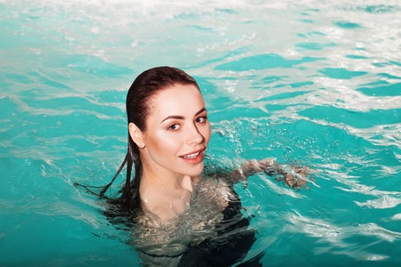 Happy young beauty swims in the pool alone. Spa and relaxation, luxury hotel. Beautiful girl portrait above the water, close-up 스톡 콘텐츠