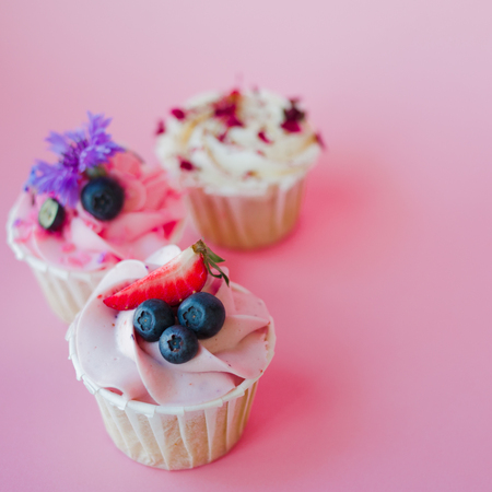 set of delicious cupcakes with different fillings and cream. Three muffin's with cream on a pink background, copy space