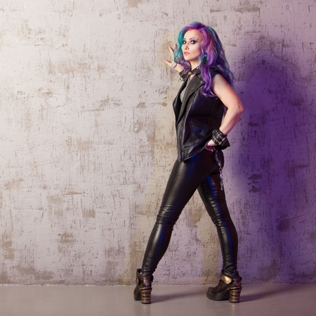 Daring rebel rocker, in black leather clothes with colored hair. Young stylish woman with trendy gradient toning hair, purple and blue 版權商用圖片
