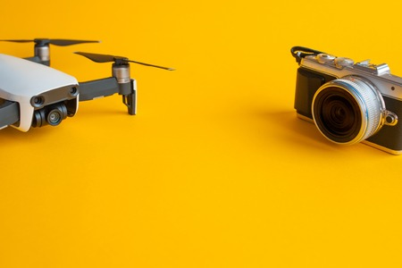 Drone for aerial photography and mirrorless camera set to create cool pictures. Yellow background and copy space