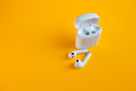 New wireless headphones in the charging box, yellow background. air pods convenient contactless headphones, stylish bright background 免版税图像