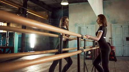 young woman dancer near the ballet Barre in the dance hall. girl athlete dancer in dark grunge room