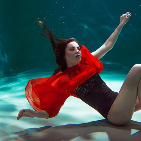 beautiful girl in a red dress dive into the water. Underwater beauty shooting. Stock Photo