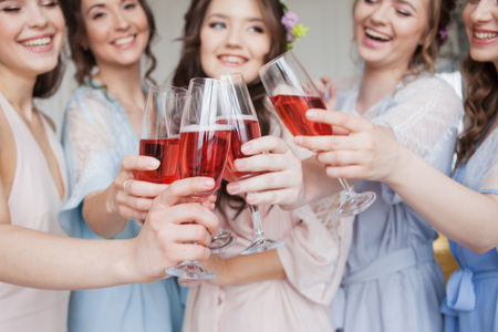 Cheerful young girlfriends raise a toast and clink glasses. Birthday party or bachelorette party, pink sparkling wine