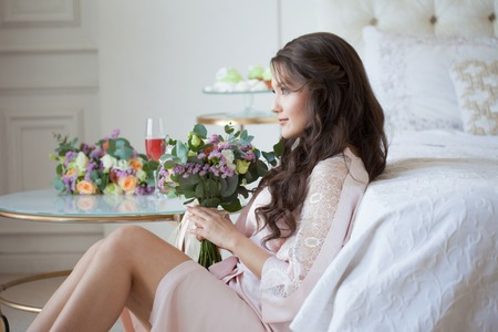 beautiful young brunette in a silk shirt sits near the bed with a bouquet of flowers. Brides morning