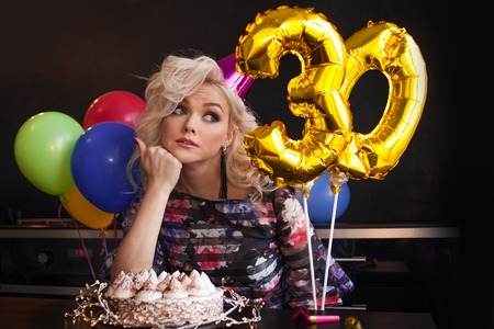 Anniversary birthday. Young beautiful blonde sitting in front of a birthday cake and sad. young woman celebrates her birthday alone
