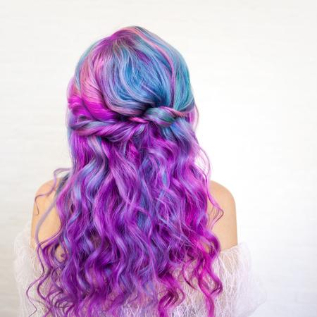 Rückansicht eines stylischen Jugendmädchens mit heller Haarfärbung, Ombre mit blauvioletten Schattierungen. Haarpflege mit leuchtender Färbung Standard-Bild
