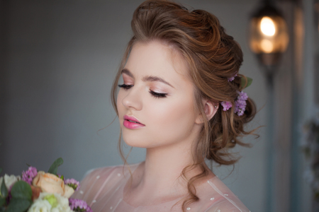 Cute young bride in pink dress. Girl with a wedding bouquet, close-up portrait