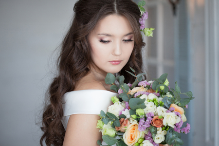 Beautiful elegant bride in white dress. A charming young woman is getting married. Portrait of a stylish bride with a bouquet