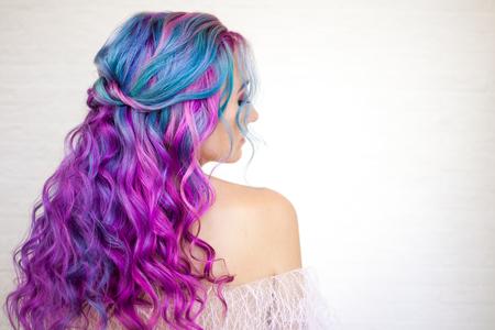 Rückansicht eines stylischen Jugendmädchens mit heller Haarfärbung, Ombre mit blauvioletten Schattierungen. Haarpflege mit leuchtender Färbung