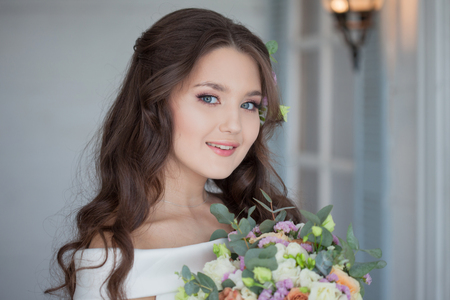Portrait of a young beautiful bride woman in a white dress and with a beautiful fluffy bouquet of fresh flowers