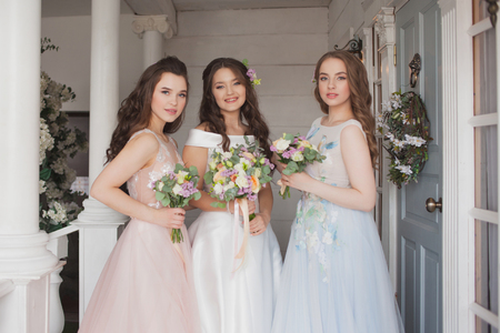 Happy girls at their best friends wedding. Beautiful and elegant bride with her friends. Beautiful young women in wedding dresses with flowers. Wedding celebration