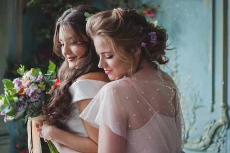 Bride and bridesmaids. Beautiful young women in dresses and with bouquets of fresh flowers.