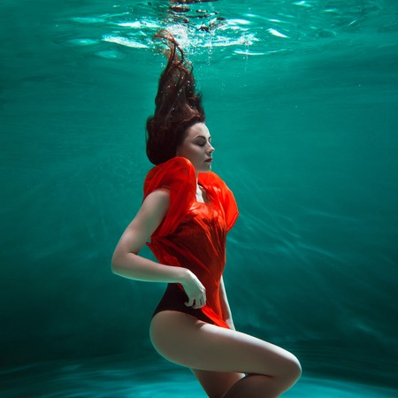 Mystical underwater portrait of a beautiful young woman in a orange dress. Girl swimming underwater, fantasy and beauty style Stock Photo