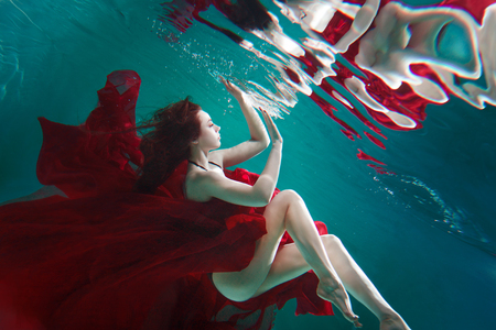 Mystical underwater portrait of a beautiful young woman in a red dress. The girl swims under the surface of the water and her reflection, Immersion concept