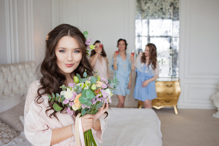 Young beautiful brunette at a bachelorette party. A young woman with a bouquet of flowers, a girl with friends celebrating. 版權商用圖片