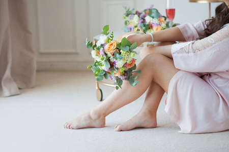 beautiful young woman in a silk shirt sits near the bed with a bouquet of flowers. Brides morning