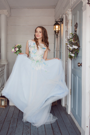Beautiful and elegant girl in a lush and fashionable wedding dress. Young bride at the wedding. blue skirt 版權商用圖片