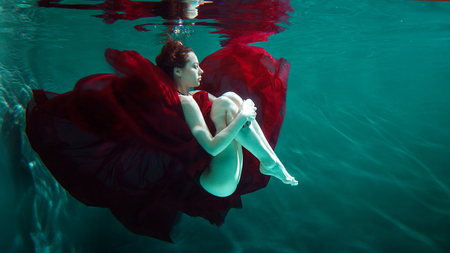 Mystical underwater portrait of a beautiful young woman in a red dress. Girl swimming underwater, fantasy and beauty style Stock Photo