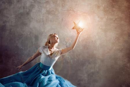 Leuchtender Stern in der Hand, greifen Sie nach dem Traumkonzept. Junge Frau, die einen Stern in der Hand hält, Träume und Ziele, Konzept