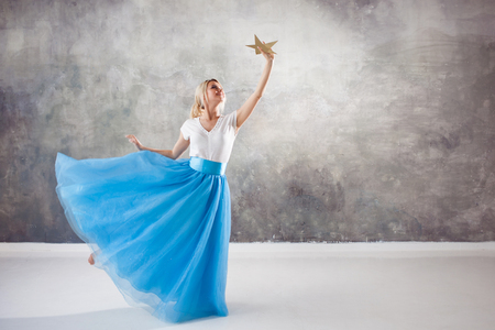 girl reaches for her dream, a concept. Young beautiful woman holding a star in her hands. Stock Photo