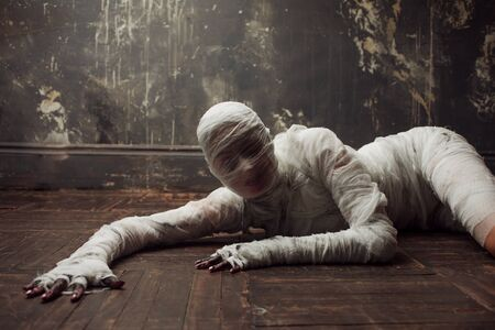 Scary mummy creeps on you. The girl with the bandage on the floor. Halloween costume