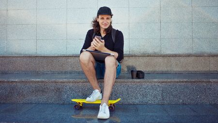 Seated young man with a closed laptop on his lap is checking a smartphone. A yellow skate is standing at his feet. Copy space