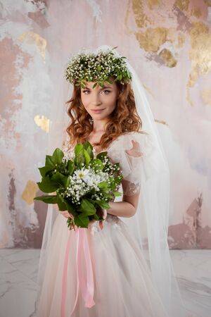 Portrait of a young beautiful woman in wedding dress with wreath and bouquet of fresh flowers. red-haired bride