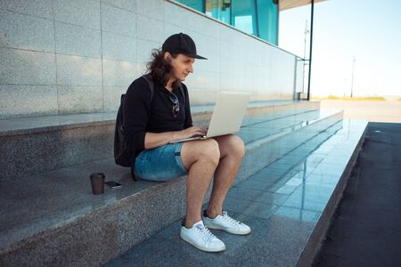 A young brunette man with long hair is sitting on the granite steps with a laptop spread out on his lap and looking thoughtfully into the distance. Summer windy day. Copy space. 版權商用圖片 - 127538491