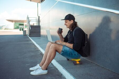 A young man with long hair and a baseball cap sits on a yellow skateboard on the asphalt, leaning his back on a gray granite wall, and and drinks coffee, while works on a laptop unfolded on his lap. 版權商用圖片 - 127538494