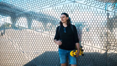 A young man in a baseball cap and denim shorts and with a yellow skate is standing against a shiny metallic reflective wall with urban ornament and a reflection of the bridge. Copy space 版權商用圖片 - 127538578