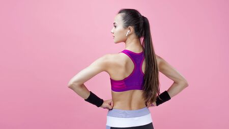 A young athletic attractive brunette girl with a ponytail in a bright tight top demonstrates her adorable athletic shape with her hands on her waist against a pink background. Copy space