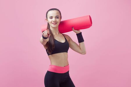 A brunette girl, attractive, is standing on a pink background, holding a yoga mat under her arm, her second hand pointing to the frame with her finger. Copy space