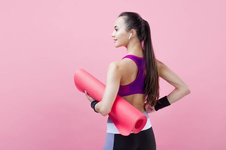 Young athletic attractive girl brunette with a ponytail in a bright tight top is standing with her back, holding a pink yoga mat under her arm, on a pink background. Copy space
