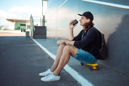 A young man in a baseball cap, with a backpack, and in denim shorts, drinks coffee while sitting on a yellow skateboard on the asphalt, next to a gray granite wall with white stripes. Side view. 版權商用圖片 - 127538597