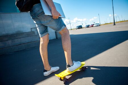 A man with a black backpack, denim shorts and a silver laptop in one hand is standing with his foot on a yellow skate board, rear view. Copy space
