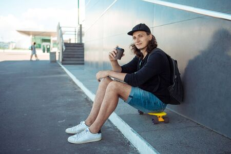 A young man in a baseball cap, with a backpack, and in denim shorts, drinks coffee while sitting on a yellow skateboard on the asphalt, next to a gray granite wall with white stripes. Side view.
